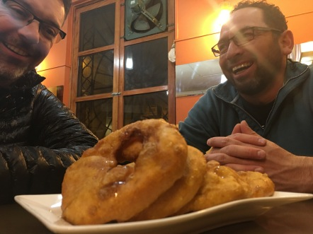 People gather over heaping piles of gigantic street donuts, glazed with honey.